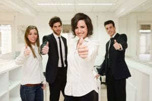 Portrait of cheerful businessteam giving thumbs up with a young woman as leader
